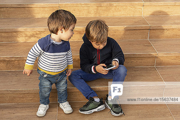 Two little boys looking at cell phone