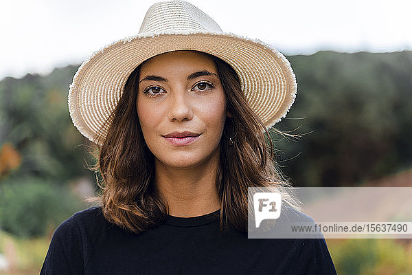 Portrait of young woman wearing summer hat