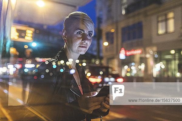 Porträt einer blonden Frau an der Straßenbahnhaltestelle am Abend mit dem Handy  Berlin  Deutschland