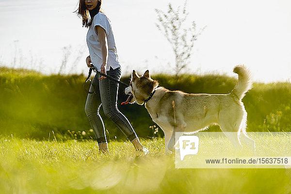 Junge Frau rennt mit ihrem Hund auf einer Wiese