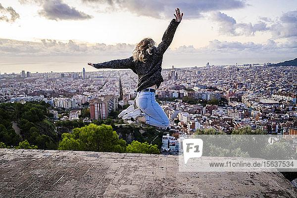 Unbeschwerte junge Frau springt bei Sonnenaufgang über die Stadt  Barcelona  Spanien