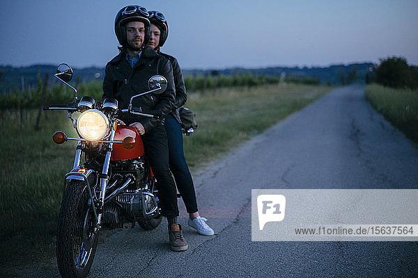 Porträt eines jungen Paares auf einem Oldtimer-Motorrad am Straßenrand