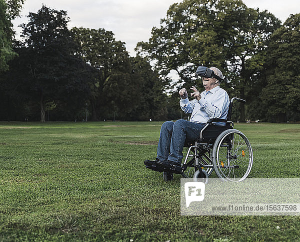 Senior man sitting in wheelchair in a park using Virtual Reality Glasses