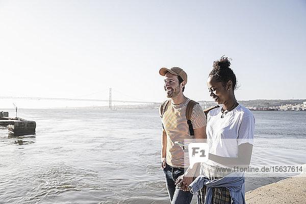 Junges Paar mit Handy auf dem Pier am Wasser  Lissabon  Portugal
