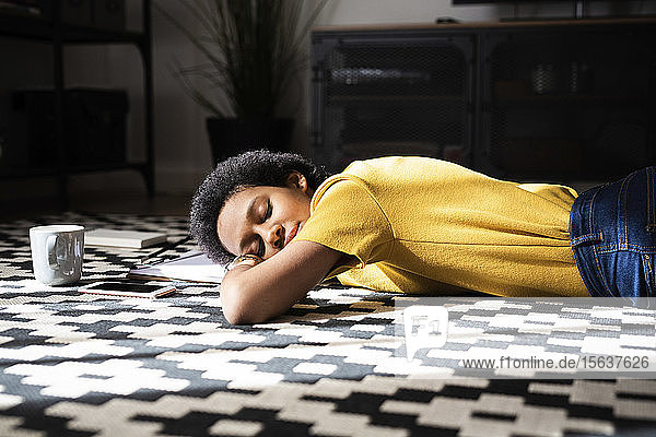 Junge Frau liegt zu Hause mit geschlossenen Augen auf dem Boden