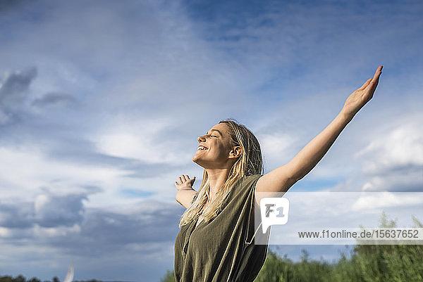 Lächelnde Frau steht mit ausgestreckten Armen im Freien