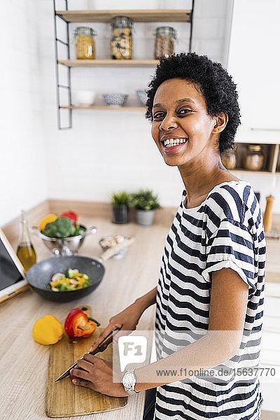 Porträt einer lächelnden jungen Frau  die zu Hause in der Küche kocht und Gemüse schneidet