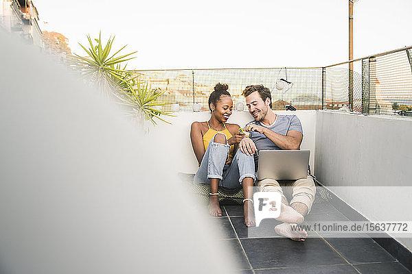 Junges Paar mit Laptop sitzt abends auf dem Dach