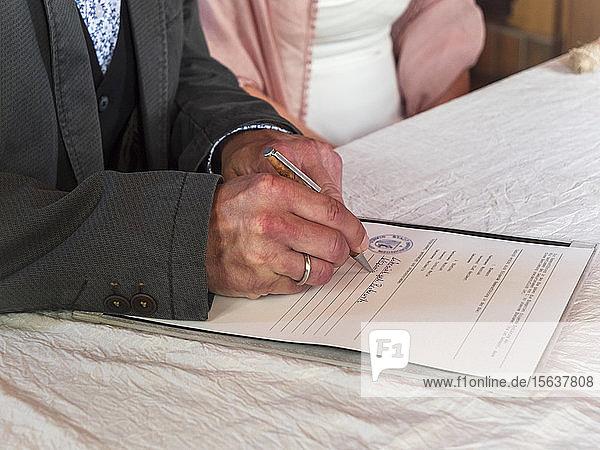 Älteres Ehepaar heiratet  Bräutigam unterzeichnet Dokument im Standesamt