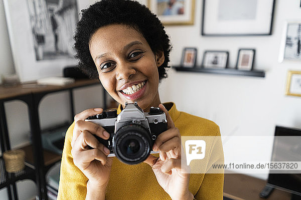 Portait of smiling young woman with vintage camera at home