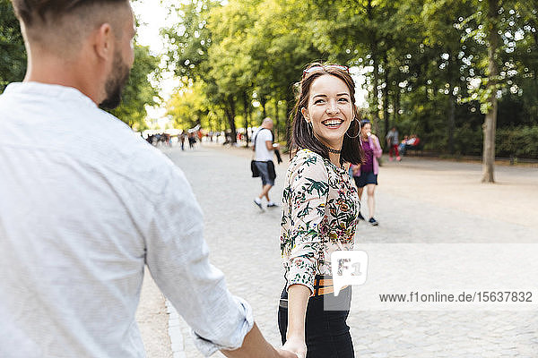 Porträt einer glücklichen jungen Frau  die Hand in Hand mit ihrem Freund in einem Park geht
