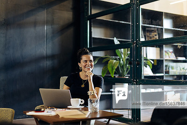 Happy casual young businesswoman with laptop in loft office