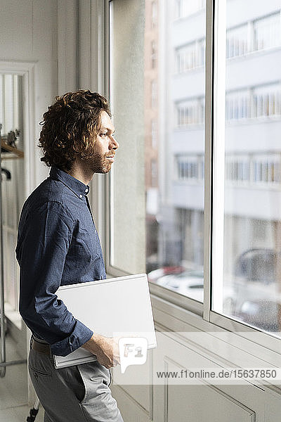 Man holding folder in a studio looking out of window