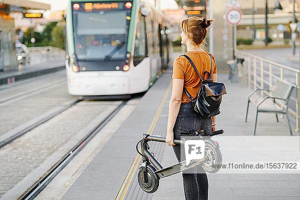 Rückenansicht einer Frau mit Rucksack und gefaltetem Elektroroller  die an der Straßenbahnhaltestelle wartet