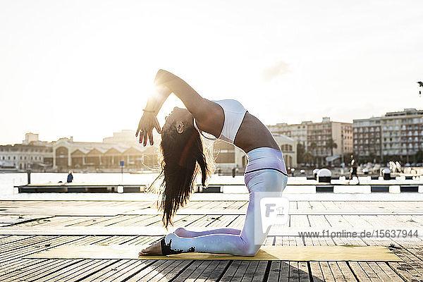 Asiatische Frau  die bei Sonnenuntergang auf einem Pier am Hafen Yoga praktiziert  Kamelpose Asiatische Frau, die bei Sonnenuntergang auf einem Pier am Hafen Yoga praktiziert, Kamelpose