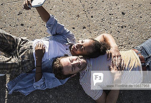 Glückliches junges Paar liegt auf dem Betonboden und macht sich ein Selfie