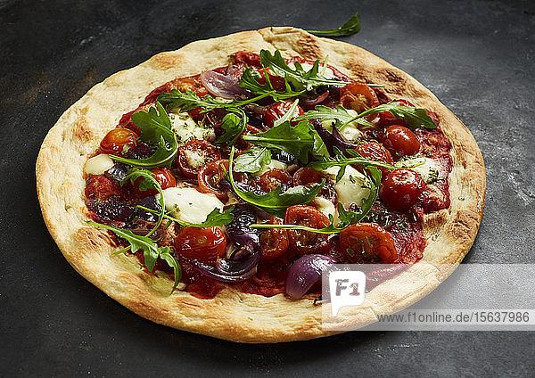 Nahaufnahme einer Pizza mit Tomaten  Zwiebeln  Mozzarella und Basilikum