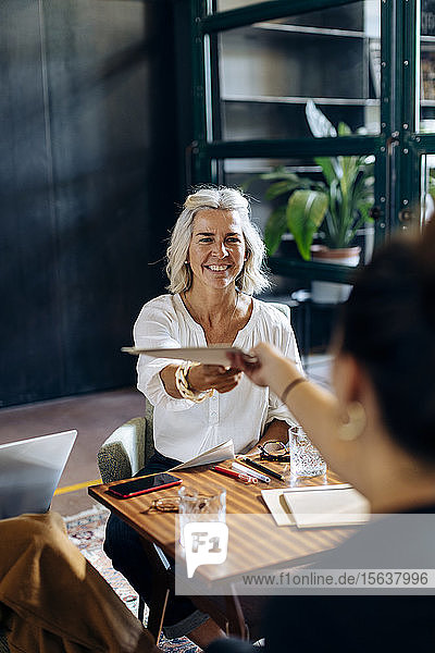 Smiling businesswoman handing over papers to colleague in loft office
