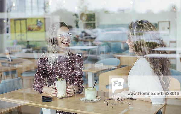 Freunde in einem Cafe  durch ein Fenster gesehen