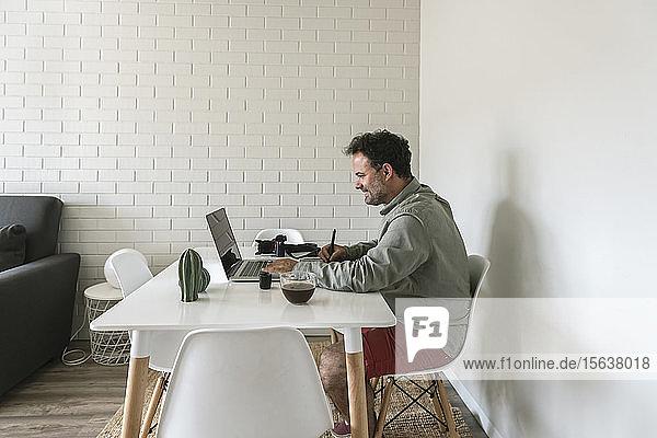 Mann sitzt am Tisch und arbeitet an Grafiktablett und Laptop