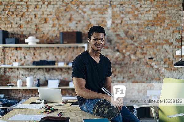 Portrait of confident young man at table in office