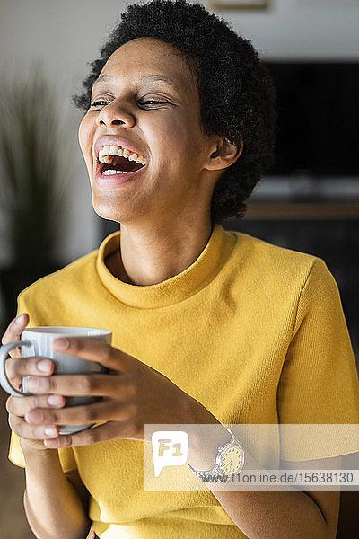 Laughing young woman holding mug at home