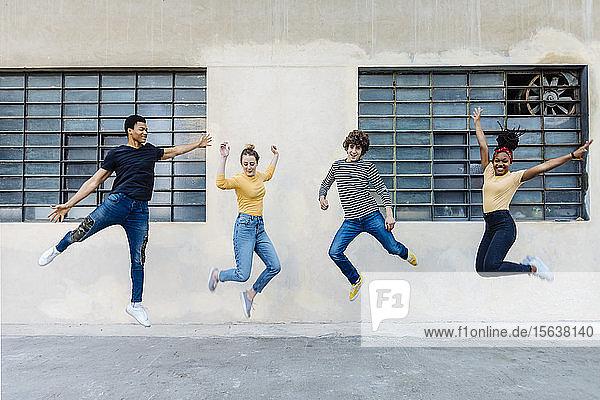 Exuberant friends jumping outdoors