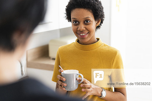 Young woman holding mug meeting friend at home