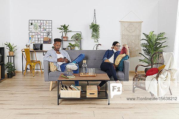 Multiethnisches Paar verbringt Zeit miteinander im Wohnzimmer