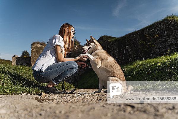 Junge Frau unterrichtet ihren Hund im Freien