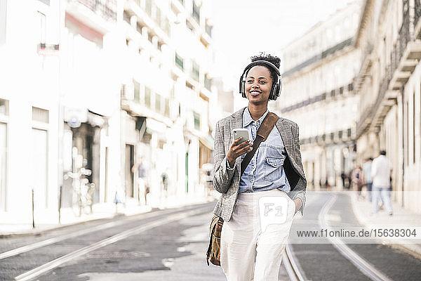 Lächelnde junge Frau mit Kopfhörer und Mobiltelefon in der Stadt unterwegs  Lissabon  Portugal
