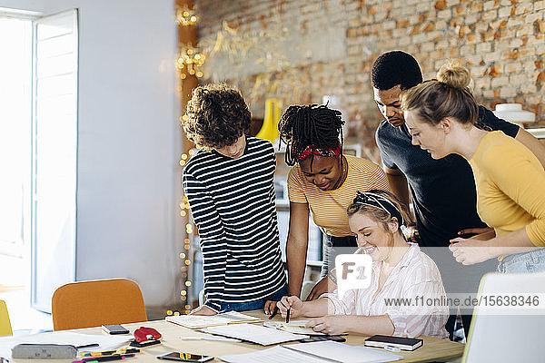 Junge Menschen arbeiten bei Tisch zusammen