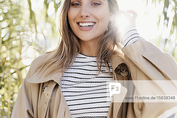 Portrait of young smiling blond woman against sunlight