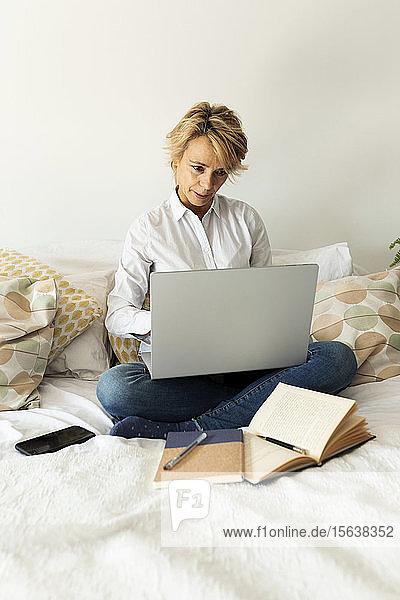 Reife Frau sitzt zu Hause am Bett und benutzt einen Laptop