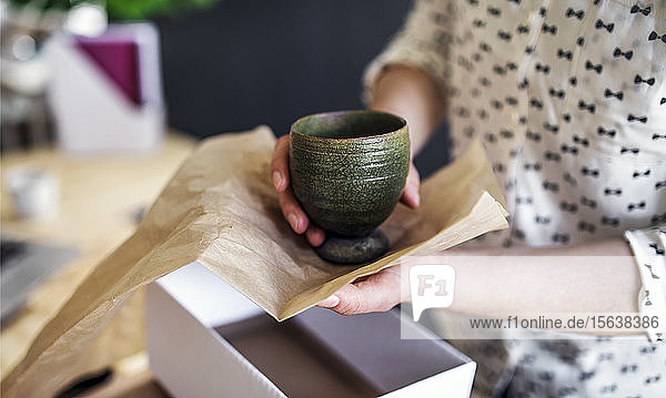 Close-up of woman wrapping an earthenware mug