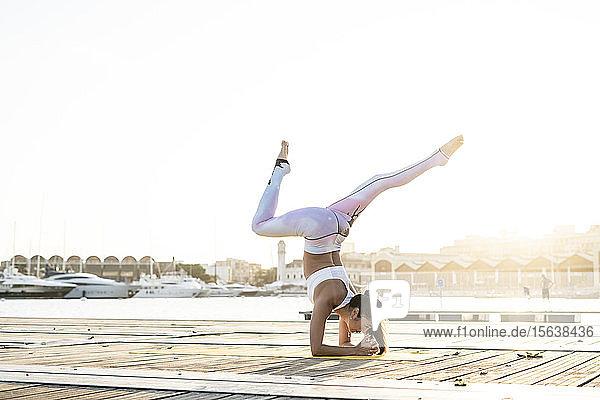 Asiatische Frau praktiziert Yoga auf einem Pier im Hafen Asiatische Frau praktiziert Yoga auf einem Pier im Hafen