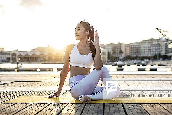 Asiatische Frau praktiziert Yoga auf einem Pier im Hafen  halbe Wirbelsäulenverdrehung bei Sonnenuntergang Asiatische Frau praktiziert Yoga auf einem Pier im Hafen, halbe Wirbelsäulenverdrehung bei Sonnenuntergang