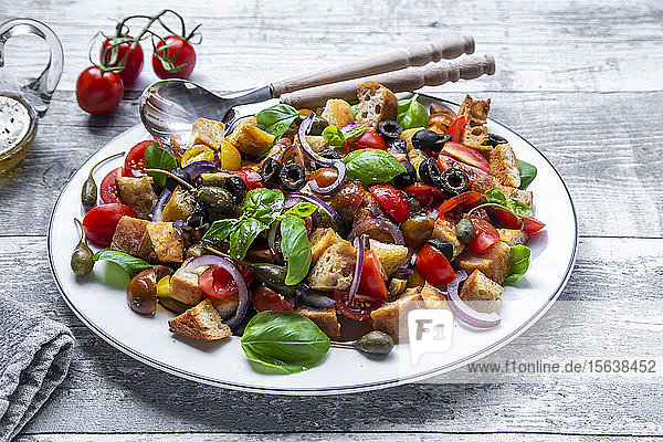 Panzanella  Italian bread salad with roasted ciabatta  tomatoes  olives  red onion  caper apples and basil on plate