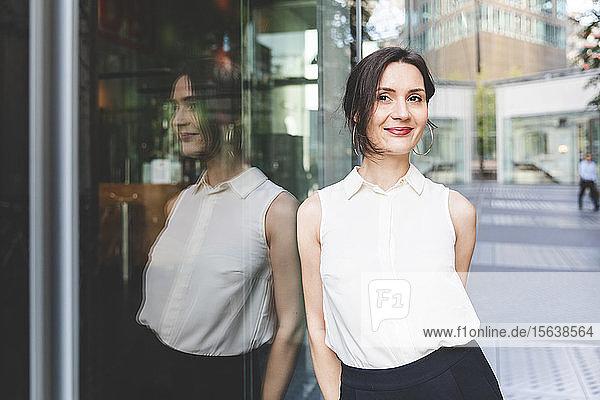 Porträt einer selbstbewussten jungen Geschäftsfrau im Spiegel der Glasfront  Berlin  Deutschland