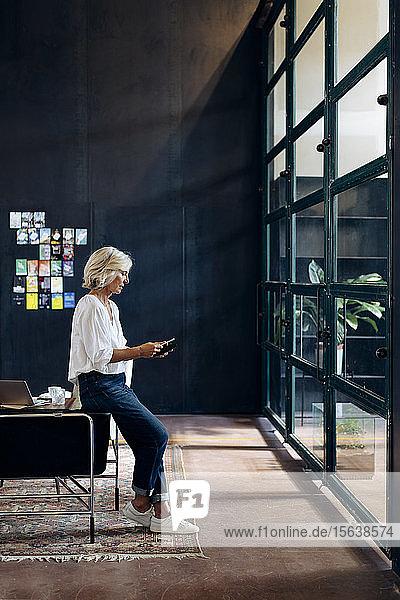 Casual mature businesswoman using smartphone in loft office