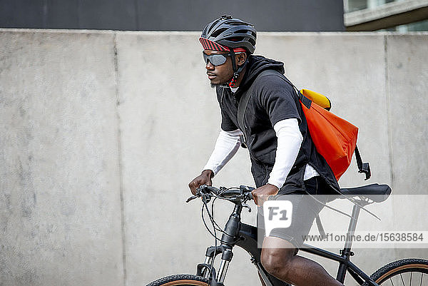 Stylish young man with messenger bag riding bicycle in the city