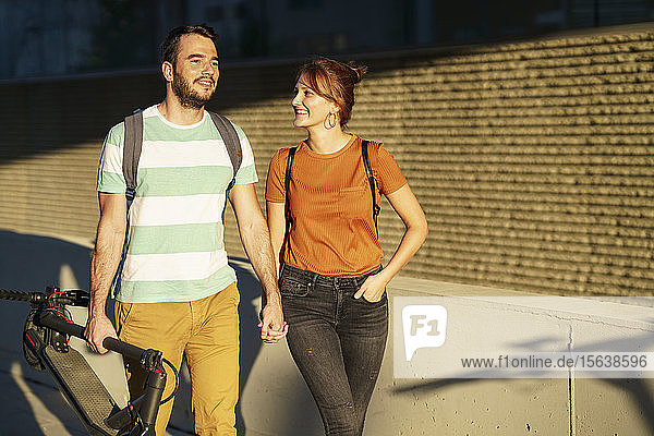 Portrait of happy couple walking hand in hand at sunlight