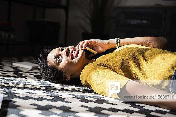 Young woman lying on the floor at home talking on the phone