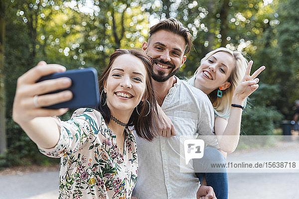 Gruppe von drei Freunden  die sich mit einem Smartphone selbstständig machen