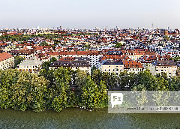Deutschland  Oberbayern  München  Bäume entlang der Isar mit Stadtgebäuden im Hintergrund