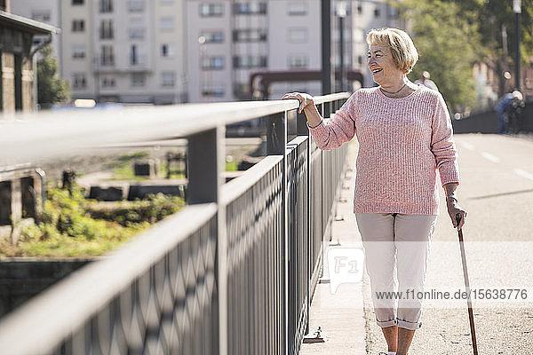 Senior woman walking on footbridge  using walking stick  looking away