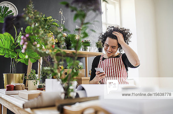 Happy young woman using cell phone in a small shop with plants