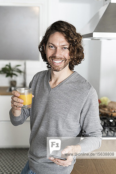 Portrait of smiling man with glass of orange juice and cell phone in kitchen at home
