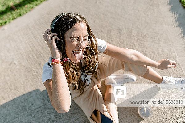 Junge Frau sitzt im Park  benutzt ein Smartphone und hört Musik mit Kopfhörern und streckt ihre Zunge heraus