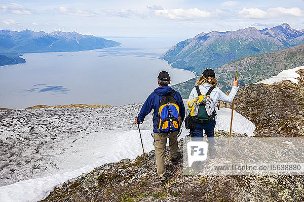 Hikers in the Chugach Mountains South of Anchorage  South-central Alaska. Summer. Couple is overlooking Turnagain Arm and the Seward Highway; Alaska  United States of America